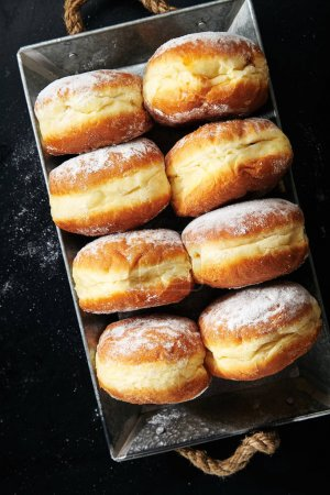 donuts with powdered sugar in metal box , close-up