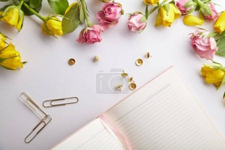 feminine workplace with rose flowers and pink notebook, spring inspiration concept