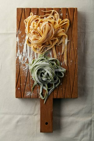 two types of handmade italian tagliatelle pasta on wooden cutting board