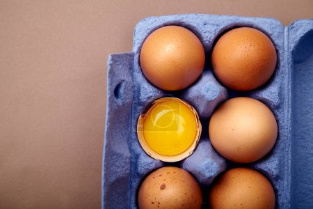 Photo for Close-up of chicken eggs and yolk in colorful violet cardboard container - Royalty Free Image