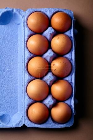Photo for Close-up with dozen of chicken eggs in colorful violet cardboard container - Royalty Free Image