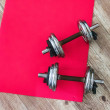 Dumbbells and gym matress on a house floor seen fr...