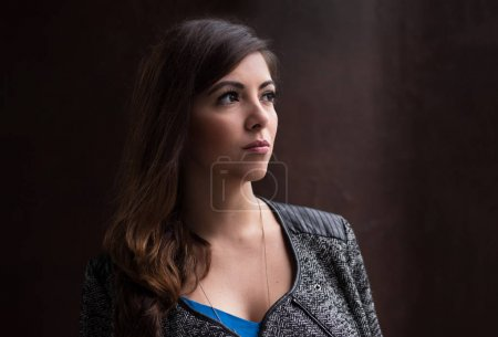 Photo for Portrait headshot of an attractive businesswoman looking away against a dark background - Royalty Free Image