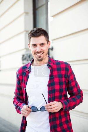 Photo pour Portrait de jeune homme attrayant joyeux regardant la caméra dans la rue - image libre de droit