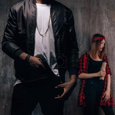 Photo pour Gars avec le gun et la jeune fille avec de l'alcool. Adolescents criminels sur fond sombre. Vie de membres de gangs - image libre de droit