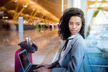 Photo pour Femme noire travaillant avec ordinateur portable à l'aéroport attendant à la fenêtre - image libre de droit