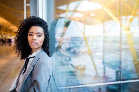 Photo pour Jeune femme noire réfléchie qui attend à l'aéroport - image libre de droit
