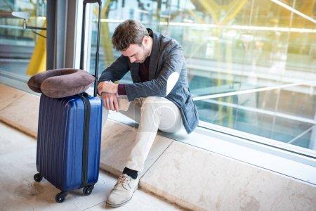Photo pour Homme contrarié à l'aéroport son vol est retardé - image libre de droit