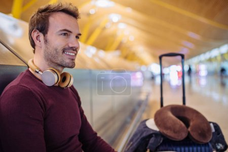 Young man waiting listening music and using mobile phone at the