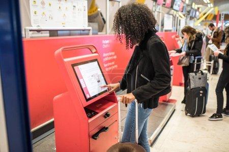 Photo pour Femme noire heureuse en utilisant le distributeur d'enregistrement à l'aéroport obtenir la carte d'embarquement . - image libre de droit