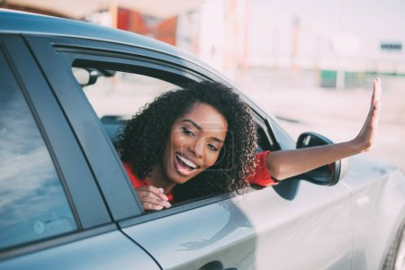 Photo for Young black woman sitting in the car smiling - Royalty Free Image