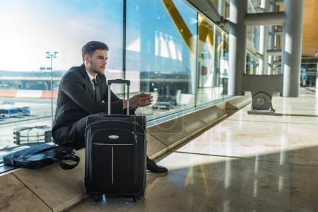 Photo pour Jeune entrepreneur bouleversé à l'aéroport en attendant son vol retardé avec des bagages - image libre de droit