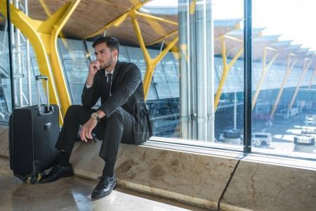Photo pour Jeune homme d'affaires en colère à l'aéroport en attendant son vol retardé avec des bagages - image libre de droit