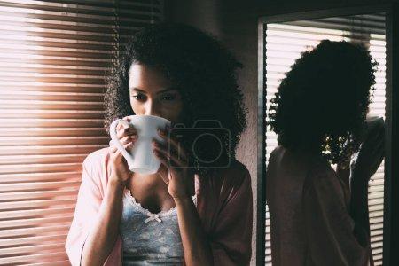 Photo pour Jolie femme noire debout à la fenêtre avec une tasse de café - image libre de droit