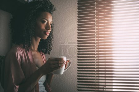 Photo pour Jolie femme noire assise à la fenêtre avec une tasse de café - image libre de droit