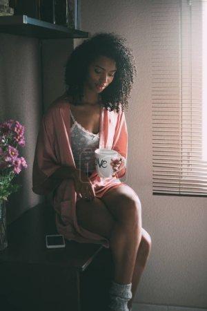 Photo pour Jolie femme noire debout à la fenêtre avec tasse de café et smartphone - image libre de droit