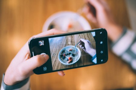 Photo for Woman taking photo of a bowl breakfast oats and fruit - Royalty Free Image