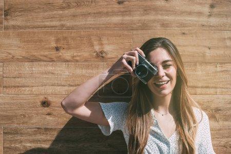 Photo pour Belle femme avec un vieil appareil photo vintage debout à un mur en bois prenant des photos - image libre de droit