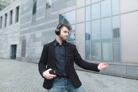 A positive man in a jacket dances to music in headphones against the backdrop of urban landscape. Joyful positive businessman is glad.