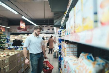 A family man chooses food at a supermarket. A man buys products in the store.