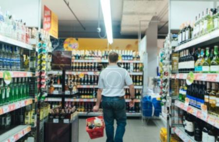 Abstract blurry supermarket. A man with a red basket makes purchases in the store. Shopping in a supermarket.