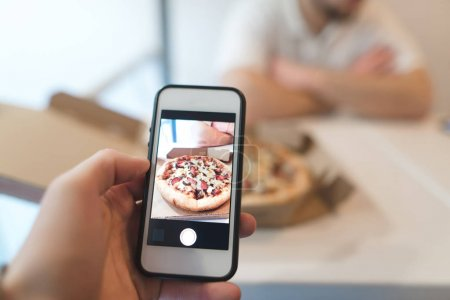 A man takes a photo of a box of pizza on his cell phone. Photo of fastfood on a smartphone.