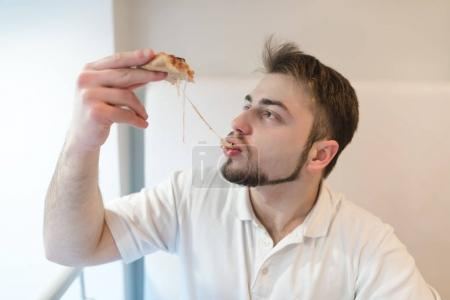 A handsome man eats a hot piece of pizza. The man eats a cheese that stretches out with a slice of pizza.