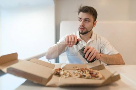 Photo for A man opens a bottle with a drink in the background of pizza. A man drinks a pizza with a cola. Drink after fast food. - Royalty Free Image