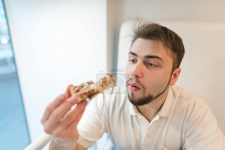 A man with a beard chewing a pizza. Student eats a tasty piece of pizza and looks at him attentively.
