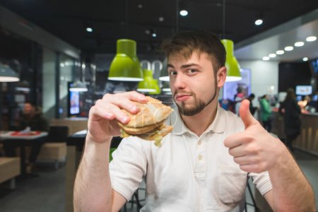 A man with a burger in his hands sits in a fast-food restaurant and shows a thumbs up. A man likes a burger.