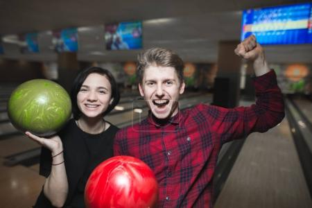 Bowling game. Happy young people with bowling balls lifted their hands upward with joy. Bowling players have won