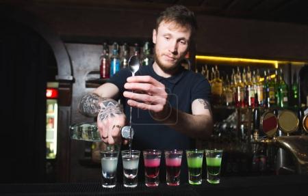 Barman creating colored alcoholic shots on bar counter