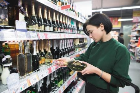 A young girl chooses wine at a supermarket A beautiful girl chooses alcohol. Shopping in the store.