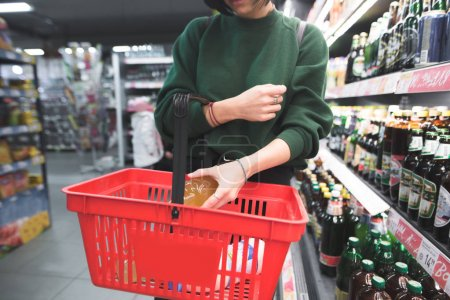 A woman puts a bottle of alcohol into a red shopping cart. The girl puts a purchase into the basket. Shopping in a supermarket.