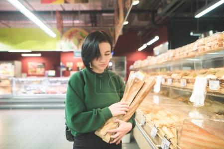 The girl buys bread at a supermarket. A girl with bread baguets in her hands walks about a supermarket.