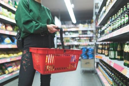 A woman with a red basket is in the supermarket. Shopping cart close-up. Shopping in a supermarket concept.