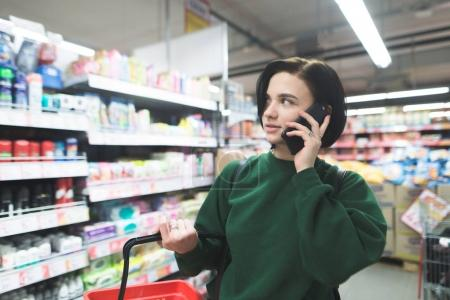 Beautiful young girl talking on the phone at the supermarket and looking sideways. The girl is shopping at the supermarket.