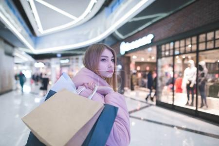 A sweet blonde with shopping bags in the yoke goes to the mall and looks to the side. Shopping concept.