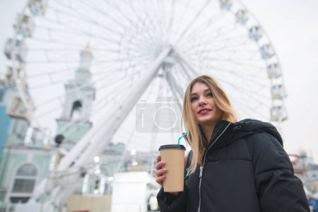 Portrait of a beautiful positive girl with a cup of coffee in hand against a background of a ferris wheel.