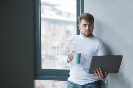 A man at the office worker stands by the window with a laptop and a cup of hot drink in his hands. Coffee break. A man works standing with a cup of coffee