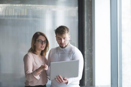 Beautiful man and woman stand in the office against the background of the wall and use a laptop. Office workers look closely at the laptop