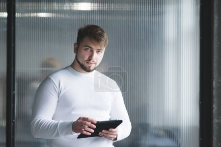 A man is an office worker standing with a tablet in his hands against the background of the wall and looking at the camera. A man in white clothes is in the office with a tablet