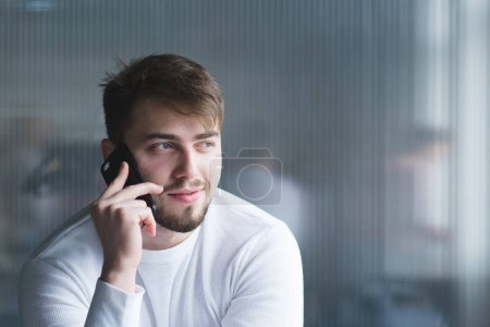 Portrait of a beautiful man in white clothes who speaks by telephone in the office on the background of the wall.