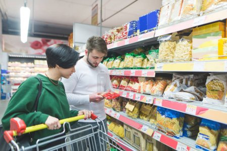 A young couple selects the products in the supermarket. The couple picks up pasta. Family shopping in a supermarket