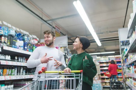 A positive, beautiful couple shopping at a supermarket and laughing. Family shopping at the store