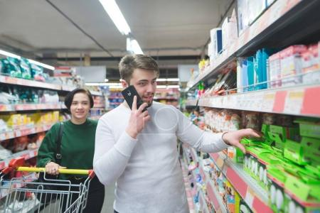 A man speaks by telephone in a supermarket and chooses goods. The girl goes with a cart at the supermarket. Shopping in a supermarket