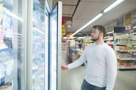 A handsome bearded man opens a refrigerator in a supermarket. Shopping in the supermarket