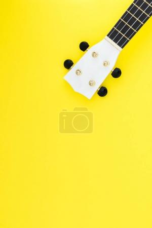 White ukulele on a yellow background and with a place for text. Musical concept. Flat Lay