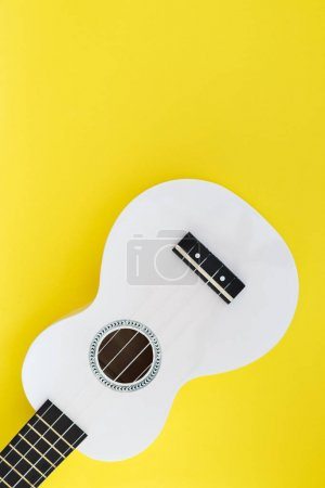 Musical concept. White Hawaiian guitar on a yellow background. Ukulele on a bright background