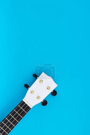 Musical instrument on a blue background. The white ukulele is on a blue background. Flat Lay Pattern